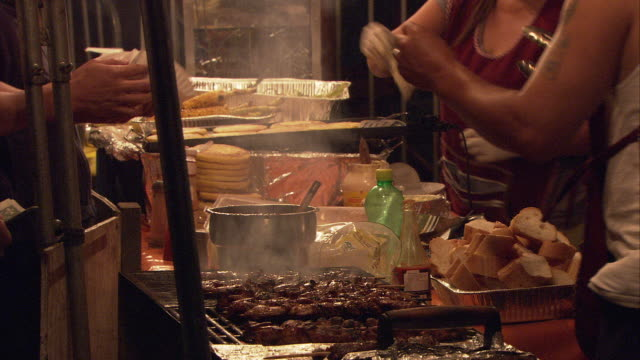 cu food vendor preparing and serving kebabs and corn in amusement park at night / hartsdale, new york, usa - concession stand stock videos and b-roll footage