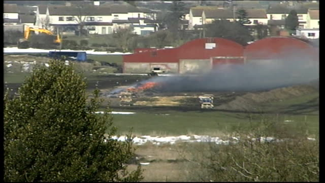 stockvideo's en b-roll-footage met general views of burning carcasses northern ireland south armagh meigh ext general views of burning carcasses sheds beyond pan to fields and houses... - foot and mouth disease