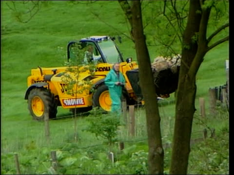 more outbreaks itn england yorkshire clitheroe seq tractor and earthmover removing dead sheep from farm int farmer driving car ext car towards along... - war in afghanistan: 2001 present stock-videos und b-roll-filmmaterial
