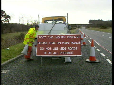 new cases government reassurances en juliet england cumbria motorway maintenance staff putting up sign on hard shoulder 'foot and mouth disease... - keep out sign stock videos & royalty-free footage