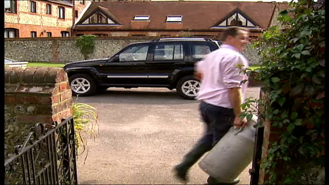 new outbreak in surrey england surrey pirbright ext hugh broom along through garden carrying milk churn broom pouring water from churn into red... - milk churn stock videos & royalty-free footage