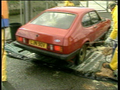 stockvideo's en b-roll-footage met foot and mouth disease outbreak in surrey confirmed 1981 men in protective suits spraying car with disinfectant car driven towards onto ferry - foot and mouth disease