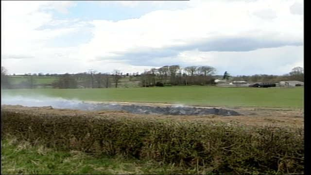 Vaccinations Funeral pyre ITN ENGLAND Cumbria Small funeral pyre smoldering in field as smoke rises CS Smoldering pyre coal and wood charred GV...