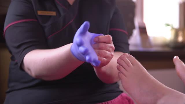 foot care, pedicurist put on sterile gloves, bare feet, close