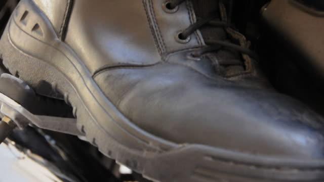 vídeos de stock, filmes e b-roll de ecu foot in black, leather shoe pressing down motorcycle peddle, los angeles, california, usa - pushing