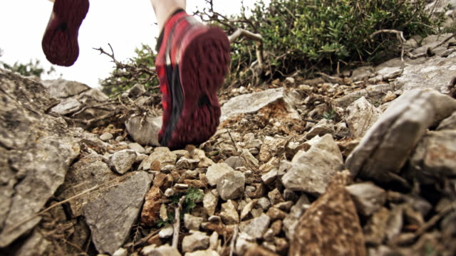 vidéos et rushes de slo mo ld pied d'un coureur féminin frappant les rochers comme elle court vers le haut de la montagne rocheuse - qui monte