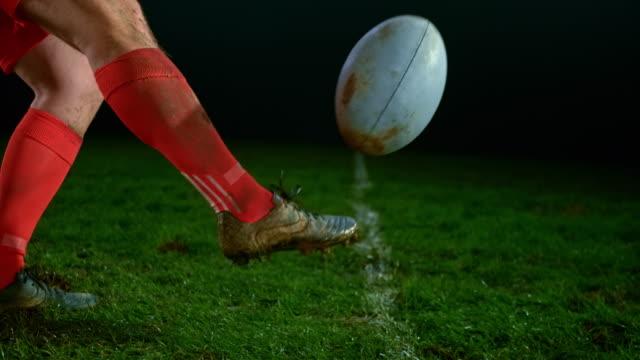 stockvideo's en b-roll-footage met slo mo voet van een mannelijke rugbyspeler schoppen de bal - ball