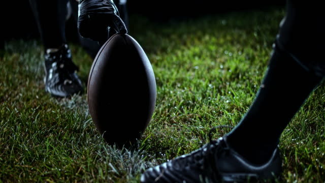 slo mo foot of an american football player kicking the ball - american football ball stock videos & royalty-free footage