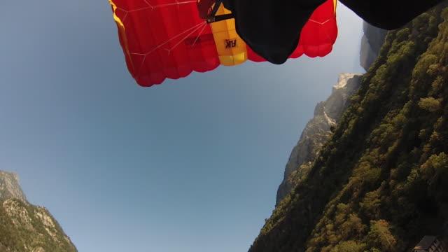 foot pov as parachuter glides towards his landing - fallschirm stock-videos und b-roll-filmmaterial