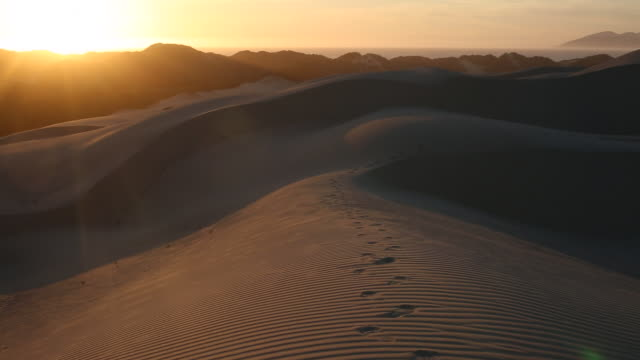 Foot prints and people walking on the open sand dunes with bright sun shining.