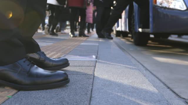 foot profile of a working man waiting for a bus from the bus stop in seoul - profil redigerat segment bildbanksvideor och videomaterial från bakom kulisserna