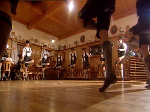 Foot stomping male German folk dancers in circle perform Schuplatter Bavaria