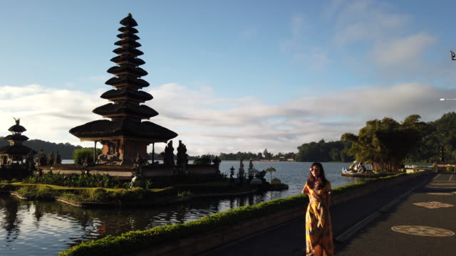 4k footage a young girl in yellow dress standing in front of pura ulun danu bratan, bali, indonesia - pura ulu danau temple stock videos & royalty-free footage