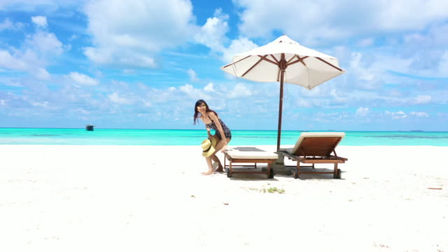 4K footage aerial view of a girl lying on the beach day bed with beautiful sea and sky
