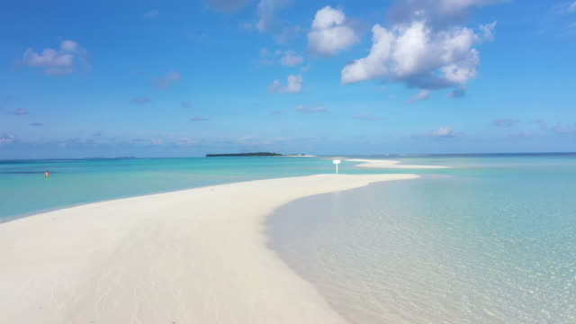 4K footage aerial view of a girl walking on the beach with beautiful sea and sky in Maldives