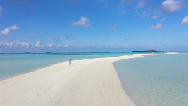 vídeos de stock, filmes e b-roll de 4k footage aerial view of a girl walking on the beach with beautiful sea and sky in maldives - cadeira de praia