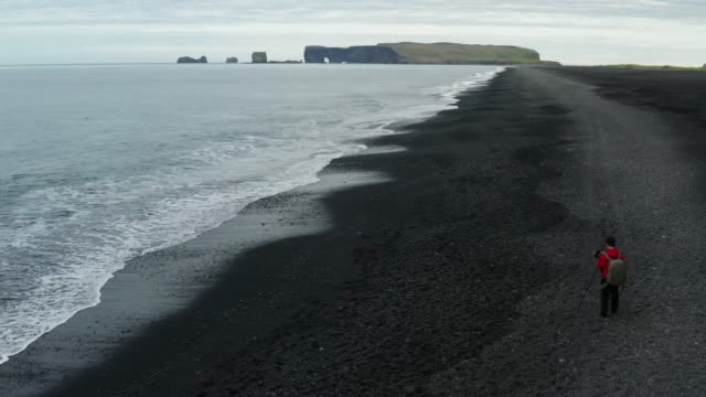 4k footage aerial view of black sand beach of reynisfjara and the mount reynisfjall in the southern coast of iceland in the morning - iceland stock videos & royalty-free footage