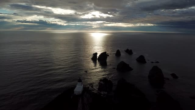 footage aerial view of sunrise at nugget point lighthouse, the catlins, south island, new zealand. - bay of water stock videos & royalty-free footage