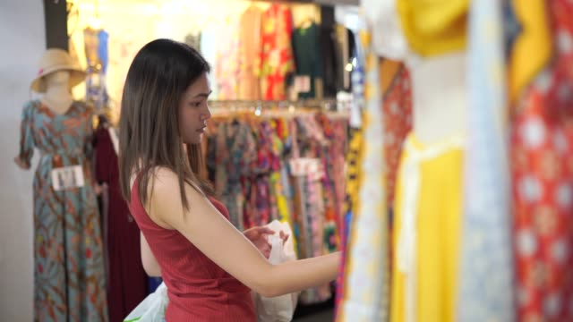 4k footage beautiful woman choosing to buy clothes - dishcloth stock videos & royalty-free footage