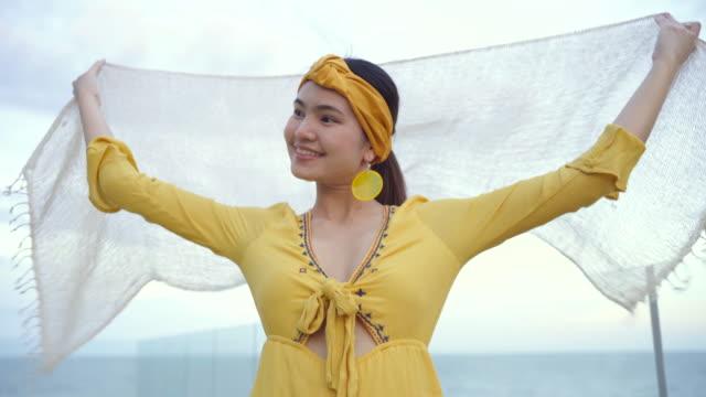 vidéos et rushes de vidéo 4k belle femme retenant le tissu blanc au vent au crépuscule. - courbe