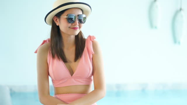 4k footage beautiful woman in bikini sitting wearing sunglasses by the pool - hat stock videos and b-roll footage
