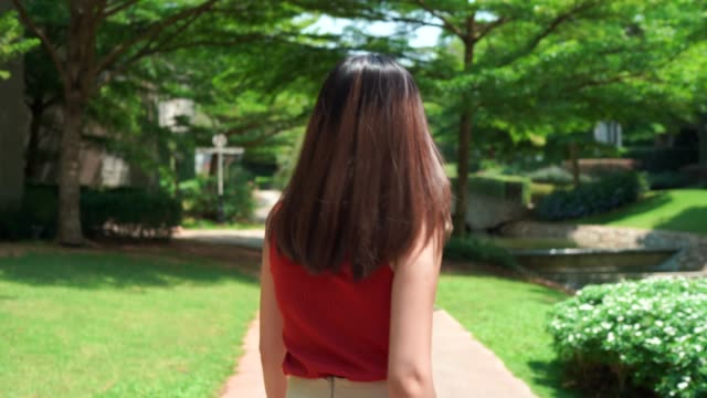 4k footage beautiful woman wearing orange dress, walking happily in the beautiful garden - elevated walkway stock videos & royalty-free footage