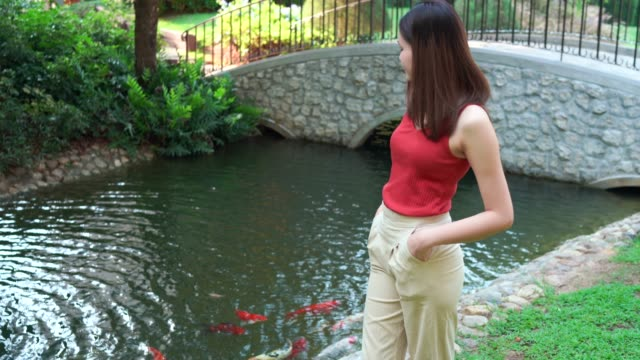 4k footage beautiful young woman is standing, relaxing beside the pond with koi fish. - natural parkland stock videos & royalty-free footage