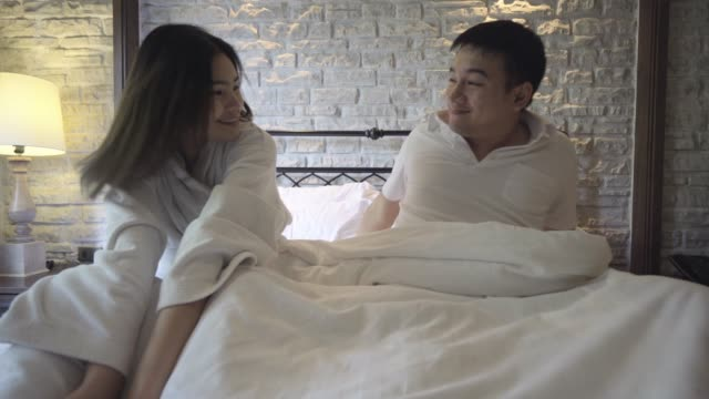 vídeos de stock e filmes b-roll de 4k footage couple waking up in the morning and being stretched in the bedroom - vestido branco