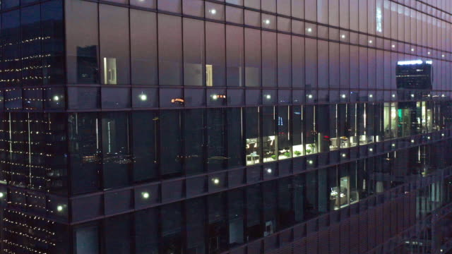 4k footage : crowded office buildings at night - edificio adibito a uffici video stock e b–roll