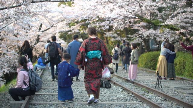 4k footage crowded people with cherry blossom tree or sakura in osaka japan - 四月点の映像素材/bロール