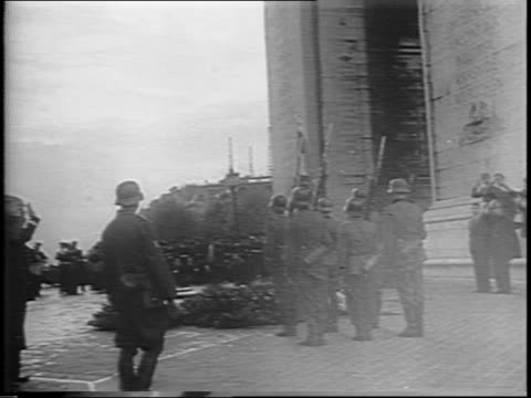 vidéos et rushes de footage from 1942 german soldiers gathered under arc de triomphe in paris france / eternal flame in foreground line of german officers in background... - arc de triomphe paris