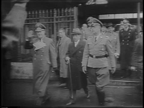 stockvideo's en b-roll-footage met footage from 1942 of german military officers on steps crowd in background / german officers walking through gate towards camera with pierre laval /... - militaire invasie