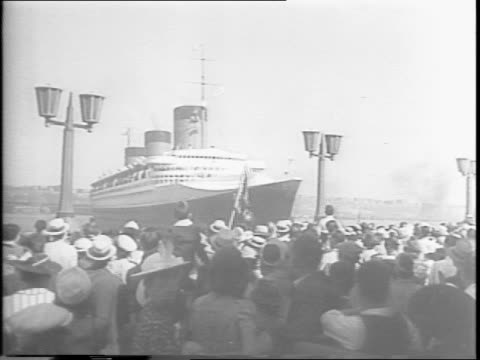 footage from 1942 sabotage of the normandie / crowds watch the normandie from the new jersey side of the harbor / overhead shot of ship passing by /... - sabotage stock videos & royalty-free footage