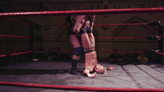 footage from an american style professional wrestling contest taking place in a small venue for an independent show a pro wrestler slingshots his... - männlichkeit stock-videos und b-roll-filmmaterial