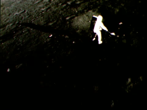 1969 montage footage from apollo 12 of either alan bean or charles conrad gathering soil samples on moon - esplorazione video stock e b–roll