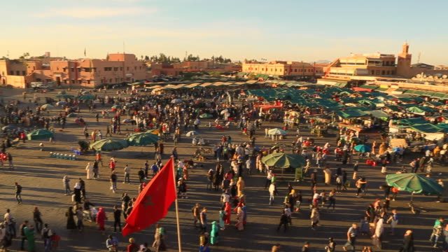 footage from elevated viewpoint of the bustle main square of jemaa el fna in marrakech city during sunset with people walking in every direction during travel vacations in morocco. - souk stock videos & royalty-free footage