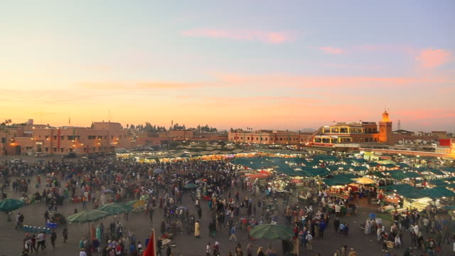 Footage from elevated viewpoint of the bustle main square of Jemaa El Fna in Marrakech city with street food during amazing sunset with people walking in every direction during travel vacations in Morocco.