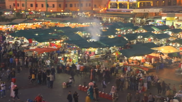 Footage from elevated viewpoint of the bustle main square of Jemaa El Fna in Marrakech city during sunset with people walking in every direction with street food market during travel vacations in Morocco.