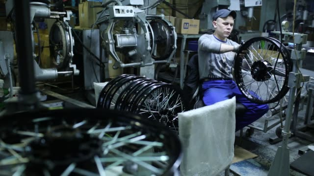Footage from inside the Irbit Motorworks Factory in Irbit Russia December 10 2015 Shots wide shot of worker covering wooden frame with cardboard wide...