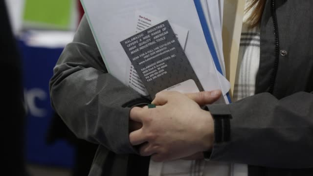 Footage from the Southwest Michigan Job Fair of a job seeker clutching employment documents as she speaks to an employer at the Kalamazoo County Expo...