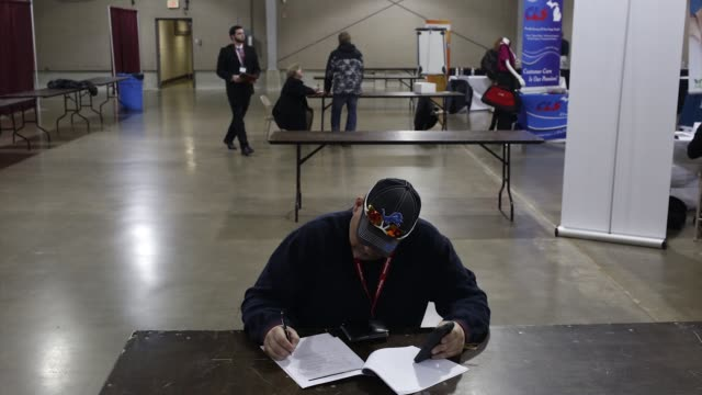 stockvideo's en b-roll-footage met footage from the southwest michigan job fair of a job seeker filling out employment documents at a table at the kalamazoo county expo center in... - banenbeurs
