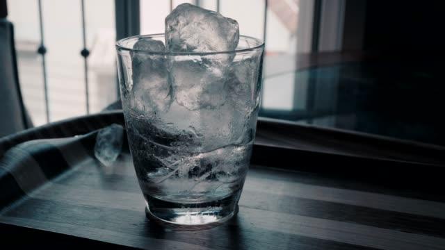 透明な水の4k 映像ガラスは、水のガラスに氷を追加します。 - カップ点の映像素材/bロール
