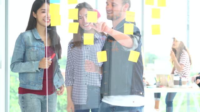 vidéos et rushes de 4k images groupe des asiatiques et des gens d'affaires diversifiés avec costume décontracté, remue-méninges et d'aider à mettre du papier de postit sur le graphique du projet ensemble dans le lieux de travail moderne, le concept de travail d'éq - employée