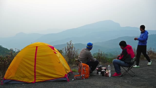 4K footage Group of asian people sitting and drinking beside tent comping in the deep forest over the scene of mountain landscape at the sunrise time, Traveler and camping concept