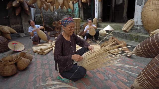 4k filmmaterial gruppe der alten vietnamesischen weiblichen handwerker machen die traditionellen bambus fische fangen oder weben auf dem alten traditionellen haus in do sy handel dorf, hung yen, vietnam, traditionelle künstler konzept - korb stock-videos und b-roll-filmmaterial