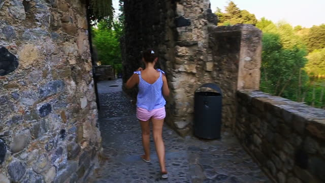 Footage in motion walking with woman visiting the old town of Besalu in Catalonia region during couple travel vacations.