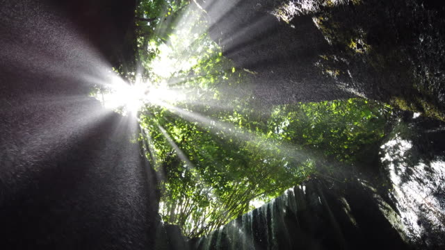 vídeos de stock e filmes b-roll de 4k footage magnificent sunbeam coming from the rocks above at tukad cepung, bali. - fluir
