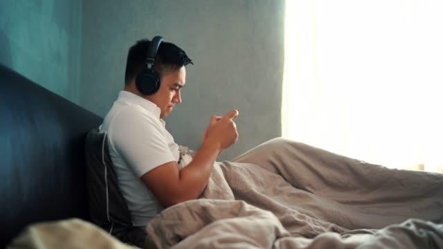 vidéos et rushes de 4k métrage hommes assis sur le lit écouter de la musique et jouer des téléphones portables à l'aide d'un casque - vidéo portrait