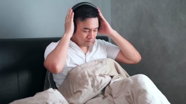 stockvideo's en b-roll-footage met 4k footage mannen zittend op het bed te luisteren naar muziek en het spelen van mobiele telefoons met een koptelefoon - videoportret
