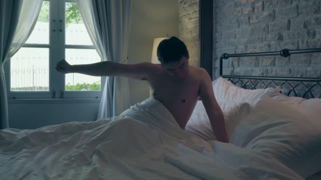 4k 映像の男性が目を覚ますとストレッチ - 前腕点の映像素材/bロール